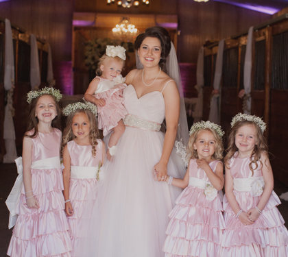 Bride standing among young children in dresses.