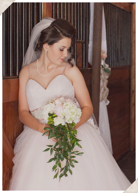 Bride leaning against a wall.
